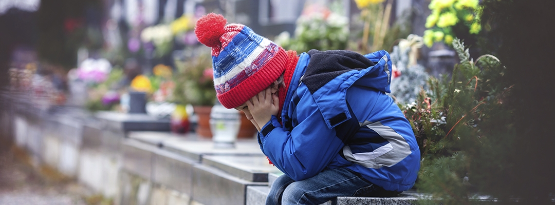 young boy grieving alone in cemetery